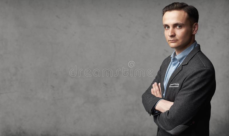 Portrait of young trendy man is standing before gray studio wall royalty free stock image