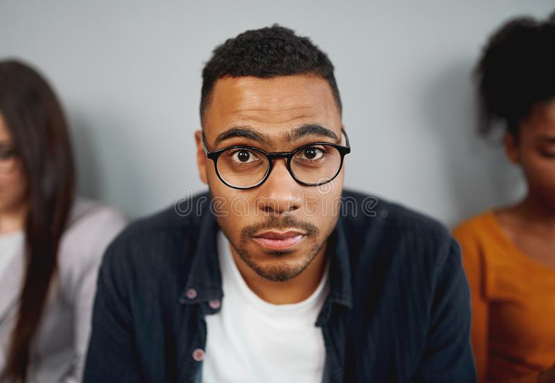 Portrait of a unemployed african american young man wearing eyeglasses waiting for the interview looking at camera royalty free stock images