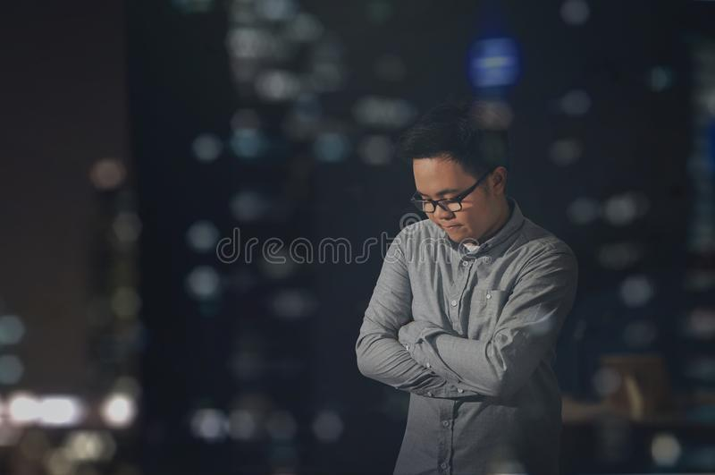 An anxious man with eye glasses at the city at night time. stock photos