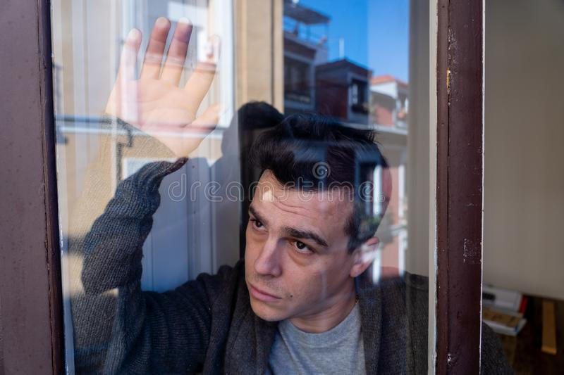 Portrait of young unhappy depressed lonely man looking stressed leaning on the window at home royalty free stock photography