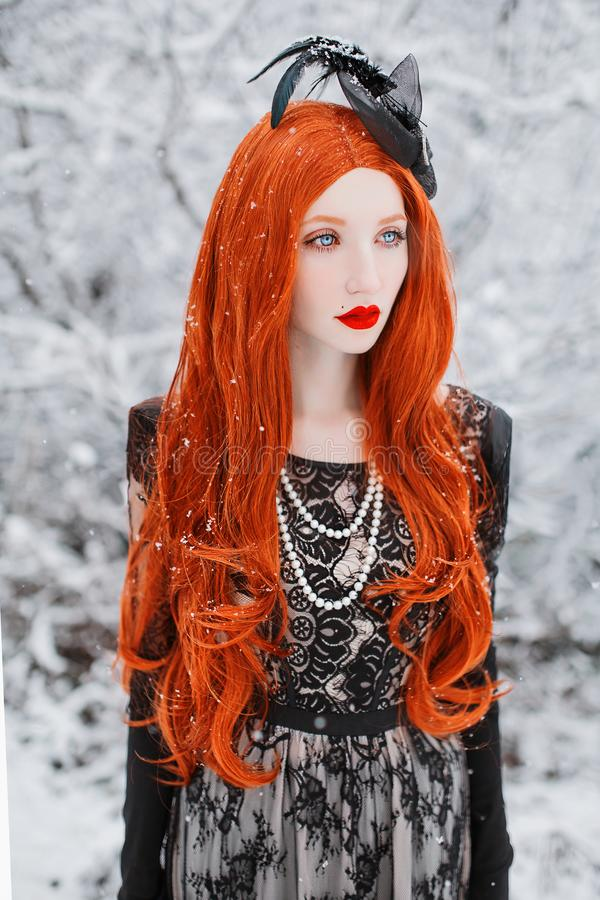 Portrait of young unusual pale girl with red hair on winter background. Beautiful redhead retro woman in black dress on a white background royalty free stock photos
