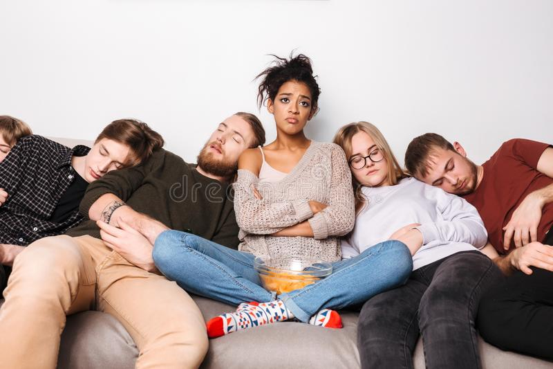 Young upset lady sitting on sofa with crisps and sadly looking aside while her friends sleeping royalty free stock image