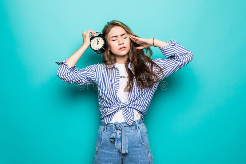 Portrait of young upset puzzled woman student in denim clothes hold alarm clock isolated on blue background. Time is running out. stock photos