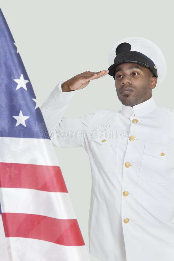 Portrait of a young US Navy officer saluting American flag over gray background