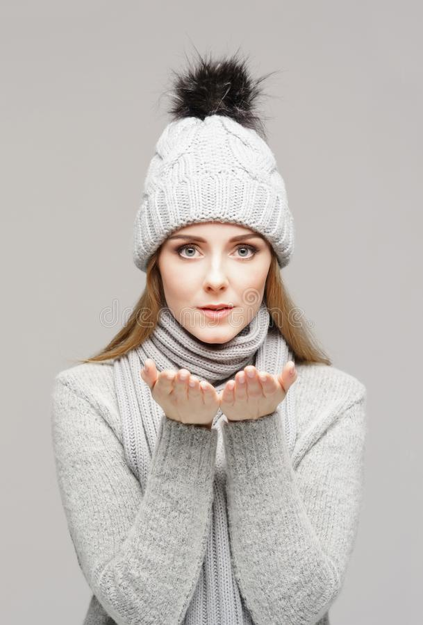 Portrait of a young and beautiful woman in a winter hat over grey background. royalty free stock images