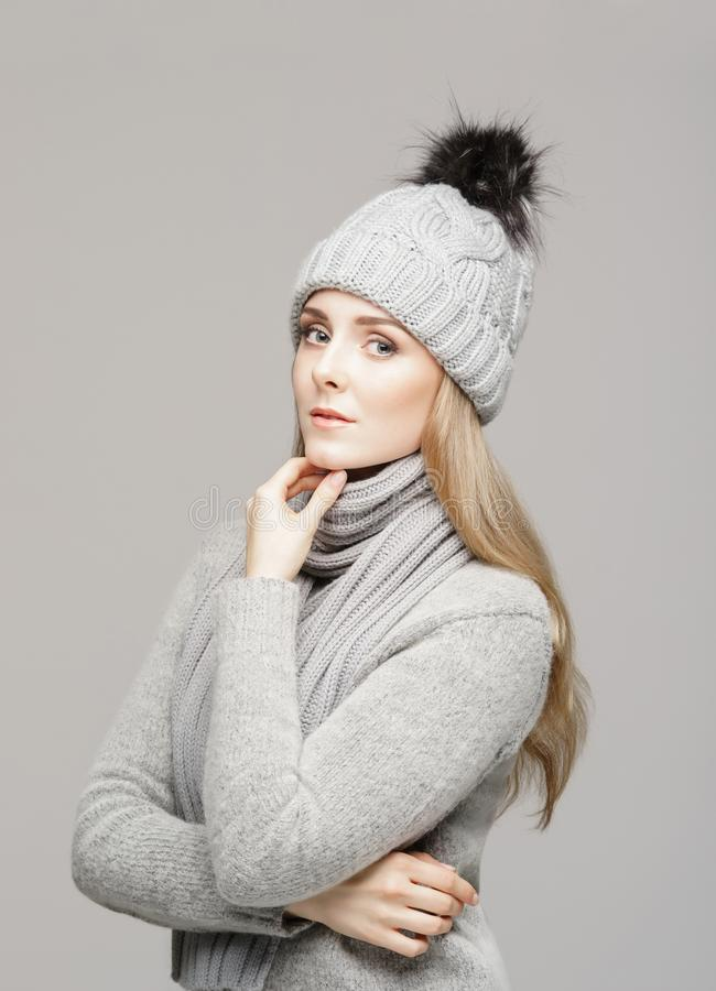 Portrait of a young and beautiful woman in a winter hat over grey background. royalty free stock photo