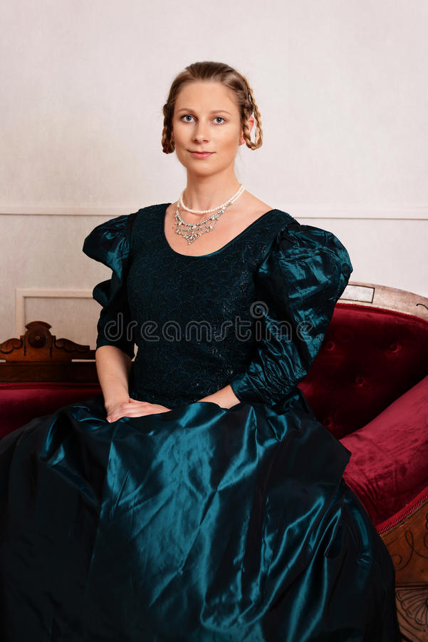 Portrait young victorian woman in green dress. Sitting on fainting couch royalty free stock photos