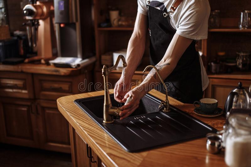 Portrait of young waiter washing his hands in kitchen at cafe royalty free stock photo