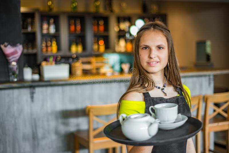 Portrait young waitress standing in cafe. girl the waiter holds in bunches a tray with utensils. Restaurant service royalty free stock images