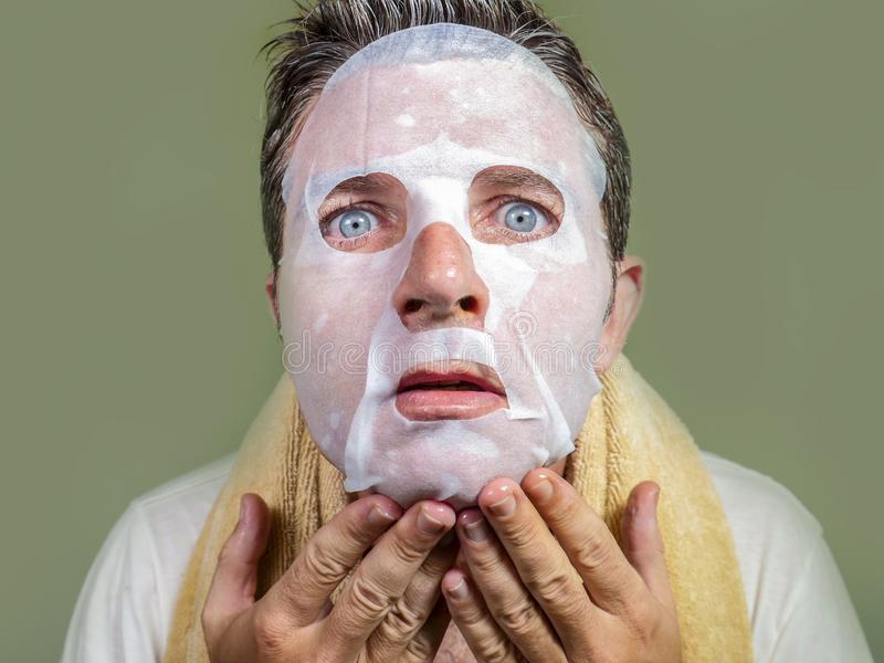 Portrait of young weird and funny man at home trying using beauty paper facial mask cleansing learning anti aging treatment in royalty free stock photos