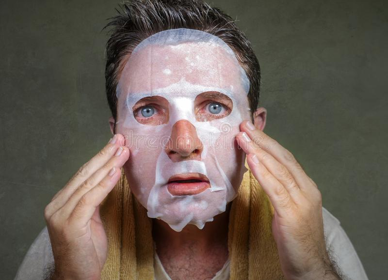Portrait of young weird and funny man at home trying using beauty paper facial mask cleansing learning anti aging treatment in royalty free stock photo