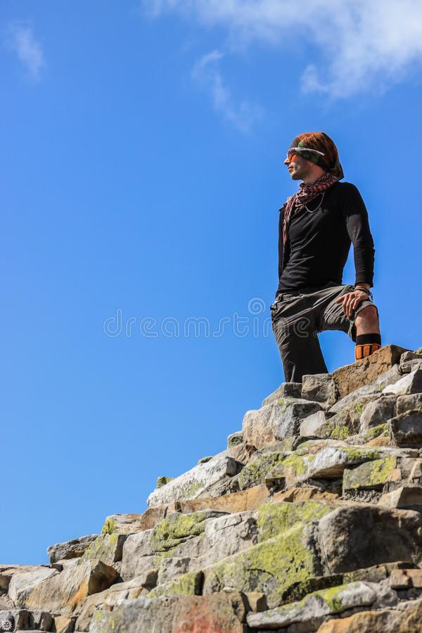Portrait of a young white Caucasian male tourist in sportswear and glasses stands on a pile of stones royalty free stock image