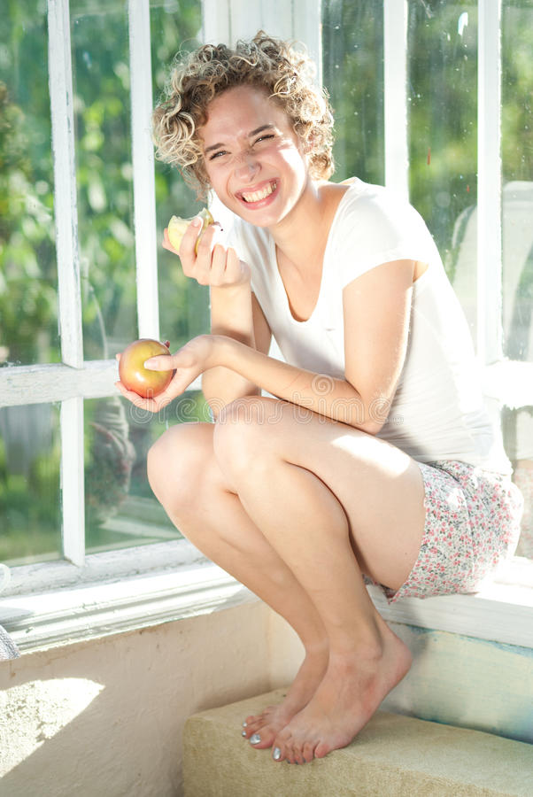 Portrait of young woman with apple at home stock photography