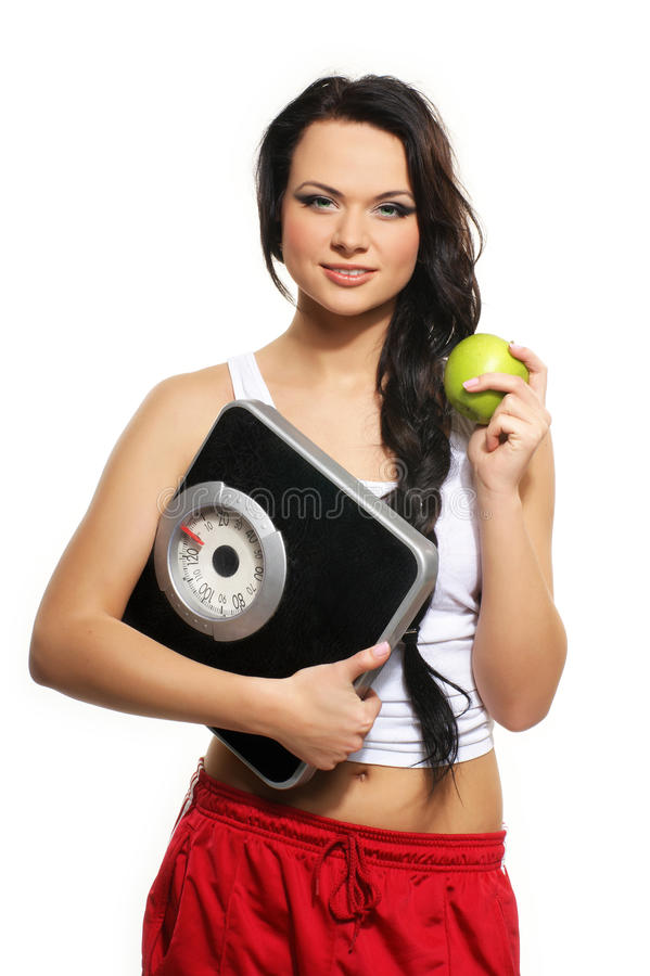 Portrait of a young woman with an apple and scales. Portrait of a young and beautiful brunette Caucasian woman holding a green apple and weight scales. The image stock photos