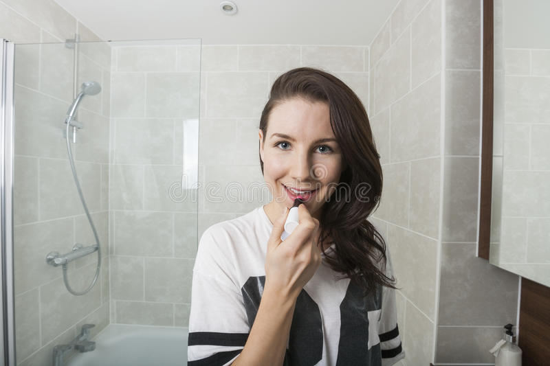 Portrait of young woman applying lipstick in bathroom royalty free stock images