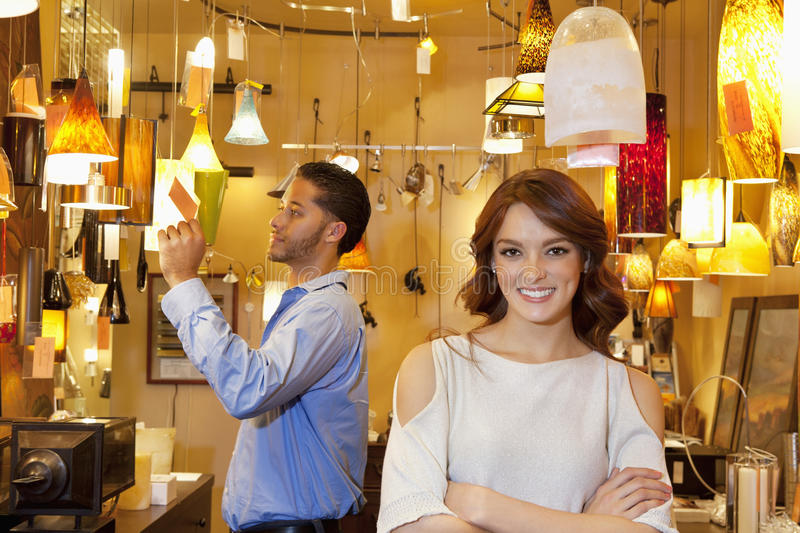 Portrait of young woman with arms crossed while man looking at price tag in background in lights store. Portrait of young women with arms crossed while men stock photography