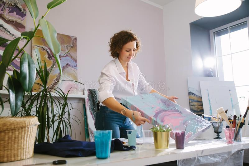 Portrait of a young woman artist in studio, working with acrylic paints on canvas. Fluid art. Portrait of a young woman artist in studio, working with acrylic royalty free stock photos