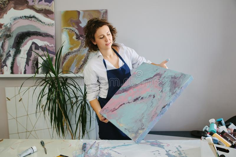 Portrait of a young woman artist in studio, working with acrylic paints on canvas. Fluid art. Portrait of a young woman artist in studio, working with acrylic stock images