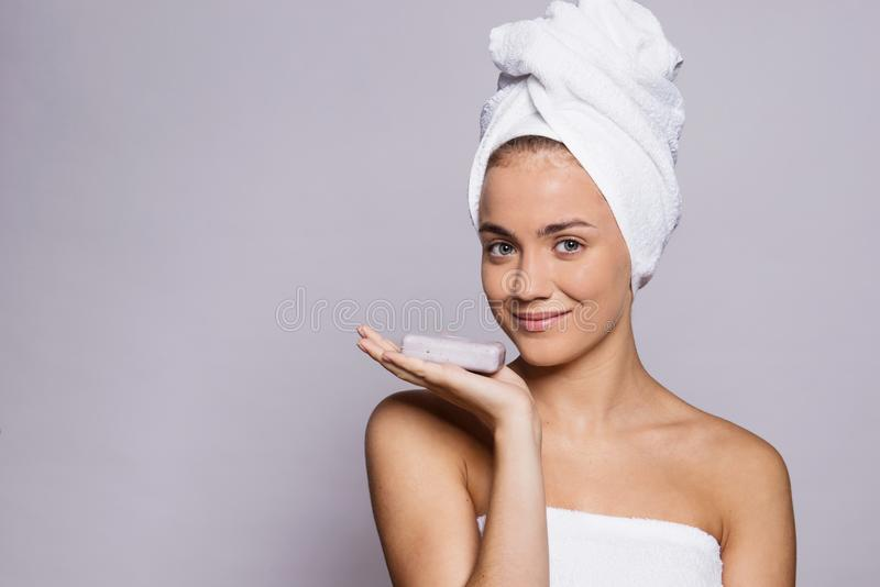 A portrait of young woman with a bar of soap in a studio, beauty and skin care. stock photos