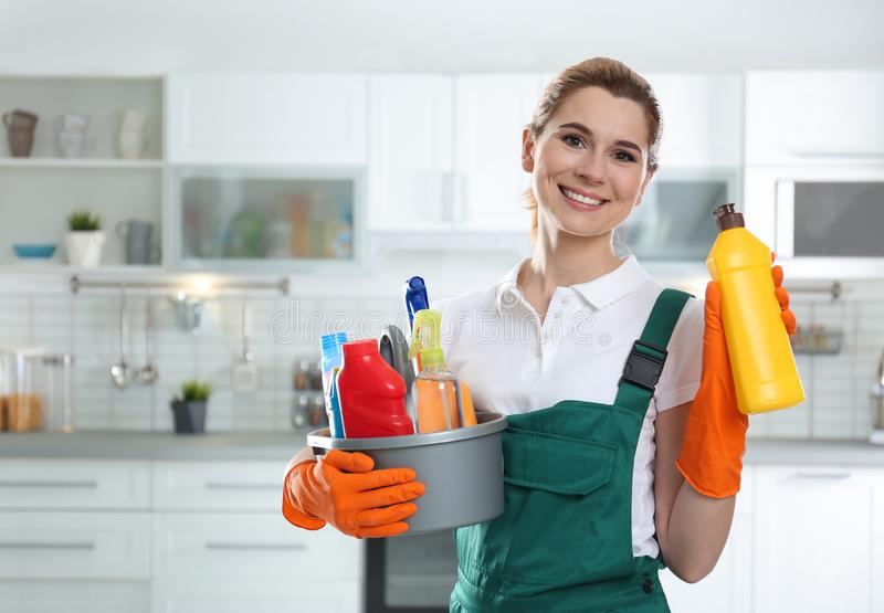 Portrait of young woman with basin of detergents and bottle in kitchen stock images