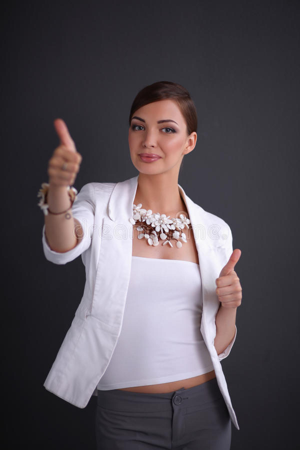 Portrait of young woman with beads showing ok,. Portrait of pretty young woman with beads showing ok, isolated on grey background stock image