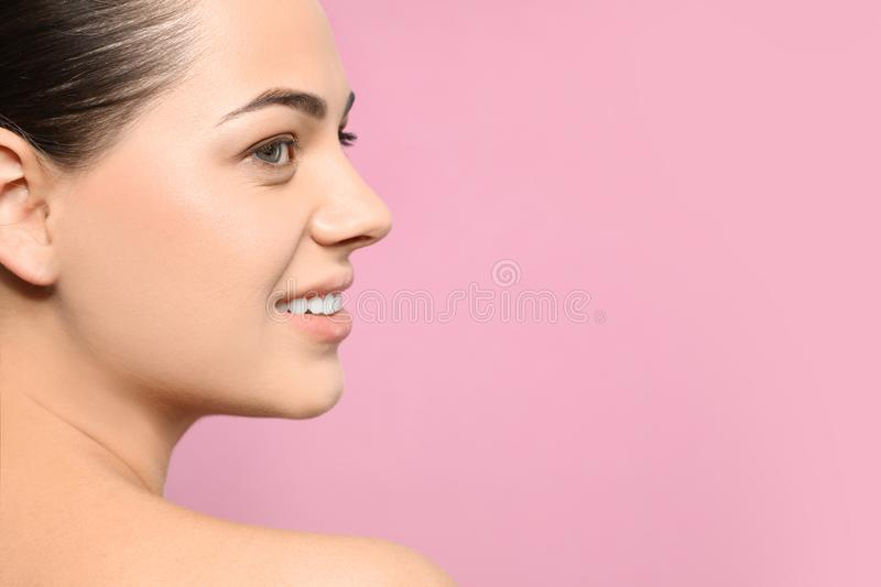Portrait of young woman with beautiful face and natural makeup on color background, closeup. Space for stock image