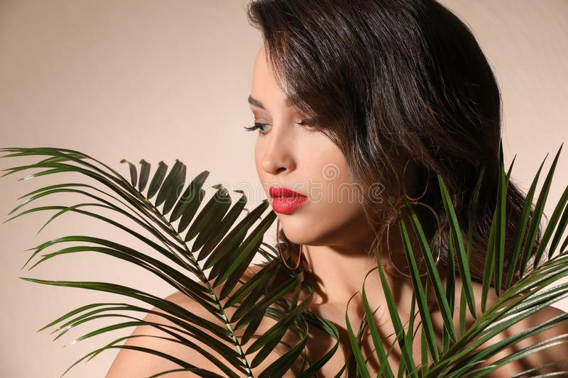Portrait of young woman with beautiful professional makeup and palm leaves on light background royalty free stock photography
