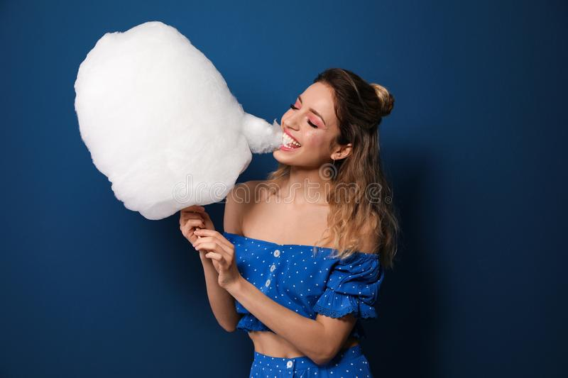Portrait of young woman biting cotton candy on background stock photos