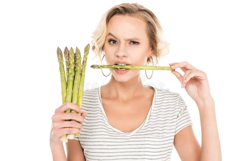 portrait of young woman biting raw asparagus in hands royalty free stock images