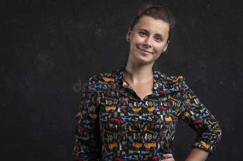 Portrait of a young woman on a black background. Attractive natural girl in a black shirt. Studio shot girl looking at the camera. stock images