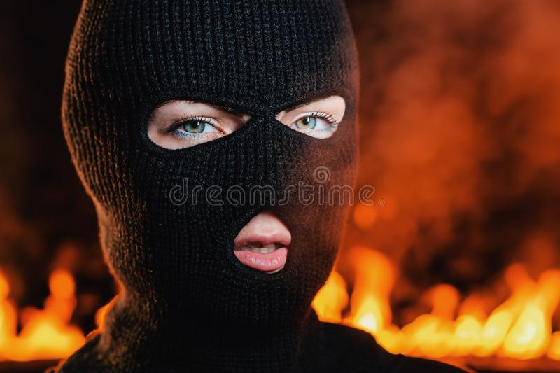 Portrait of young woman in black balaclava against backdrop of a blazing night fire. Concept of mass rallies and riots.  stock photo