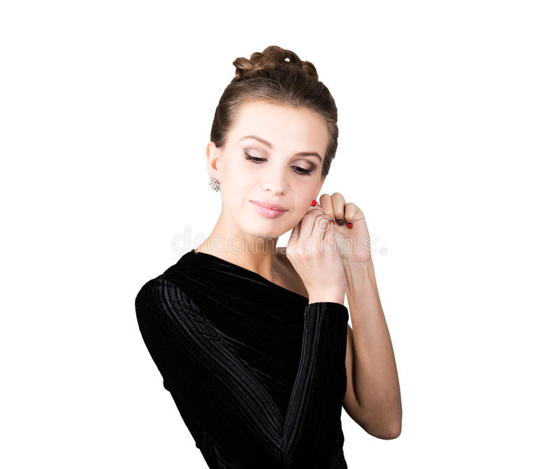 Portrait of the young woman in a black dress, which corrects earrings stock photos