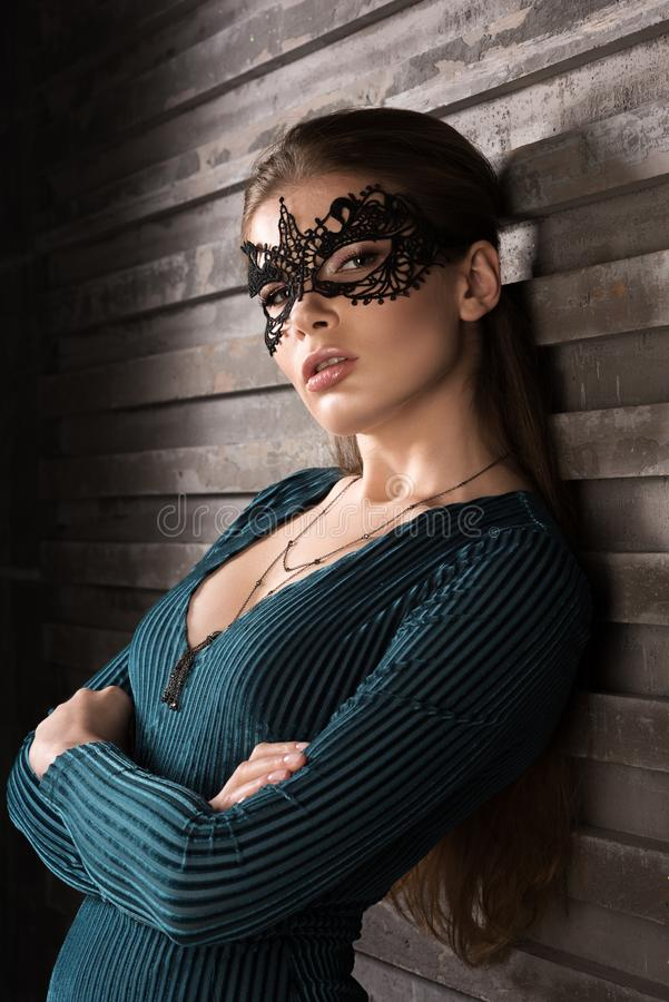 Portrait of young woman in black lace mask on her face. Professional make-up royalty free stock photos