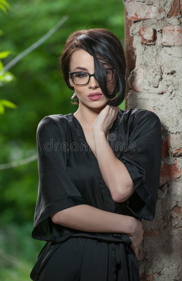Portrait of young woman in black silk dressing gown, leaning against the wall. Beautiful seductive short-haired woman royalty free stock photos