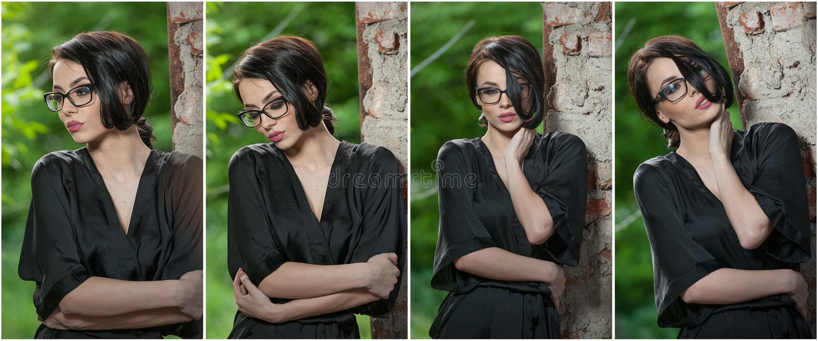Portrait of young woman in black silk dressing gown, leaning against the wall. Beautiful seductive short-haired woman, posing royalty free stock image