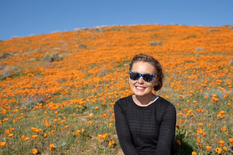 Portrait of a young woman in a black top in the wildflower field of poppies during the California super bloom.  royalty free stock photo