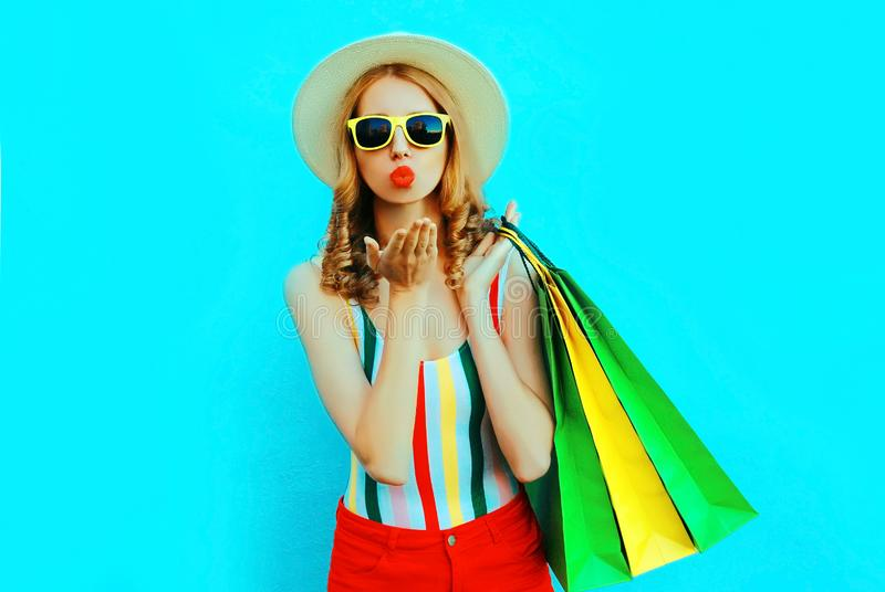 Portrait young woman blowing red lips sends air kiss with shopping bags in colorful t-shirt, summer round hat on blue wall. Background royalty free stock photos
