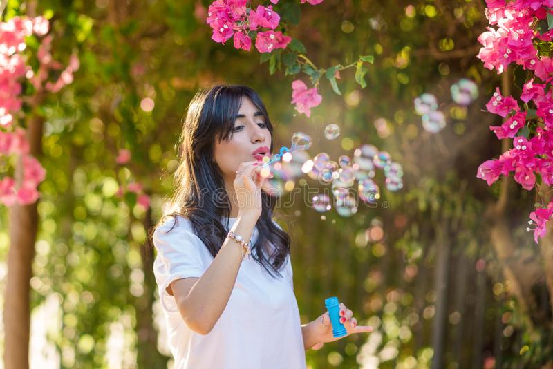 Happy beautiful young woman blowing soap bubbles outdoor. stock photo