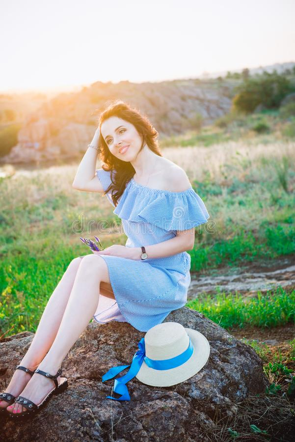 Portrait of young woman in blue romantic dress and straw hat in sun light enjoying summer sunset on nature. Calm and harmony. stock photos