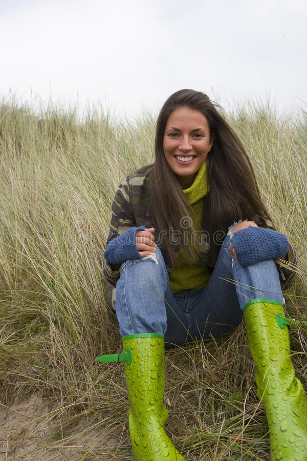 Portrait of young woman in boots sitting in grass royalty free stock image