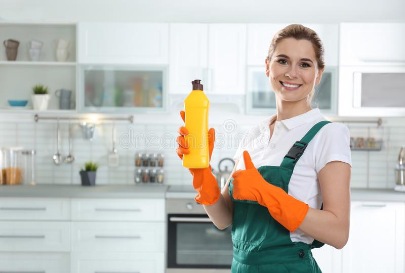 Portrait of young woman with bottle of detergent. Cleaning service royalty free stock photography