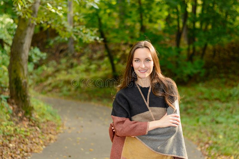 Portrait of a young woman brunette in a wool poncho Standing on a footpath in the green Park in the background in the rays of the stock image