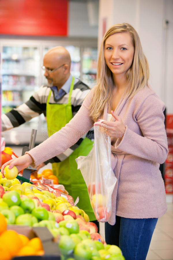 Portrait of a young woman buying fruits royalty free stock photos