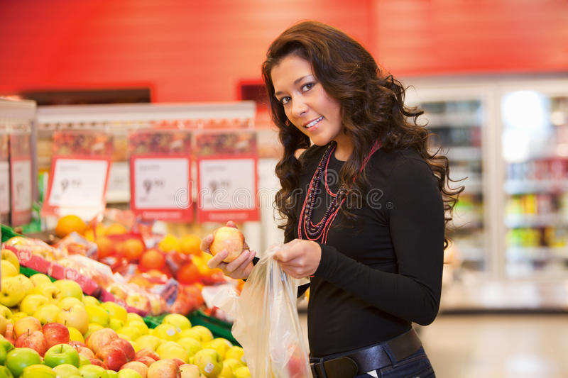 Portrait of a young woman buying fruits stock image