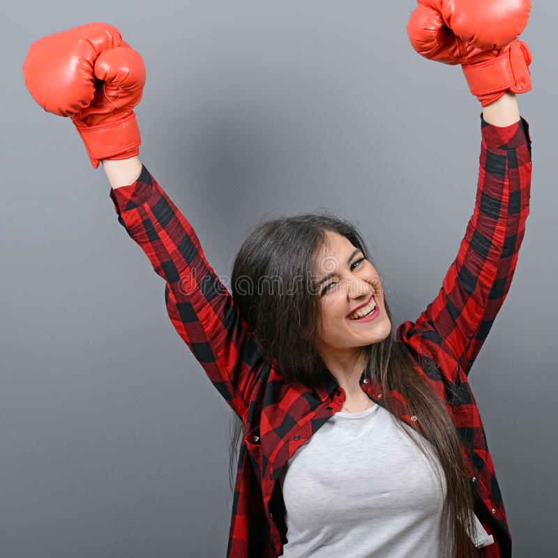 Portrait of young woman in casual clothes and hands up in air with boxing gloves celebrating as winner against gray background stock photo