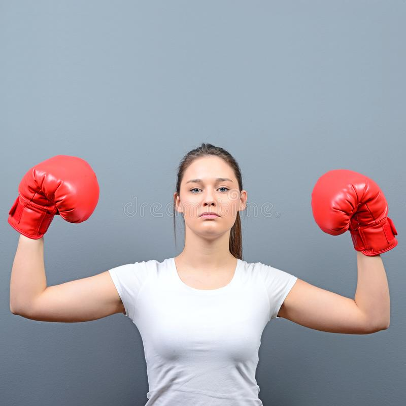 Portrait of young woman in casual clothes and hands up in air with boxing gloves celebrating as winner against gray background royalty free stock images