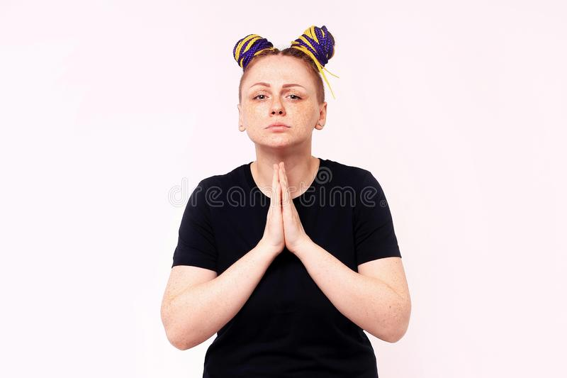 Portrait of woman in casual clothes looking camera, holding hands folded praying. The woman has dreadlocks on her head, freckles stock images