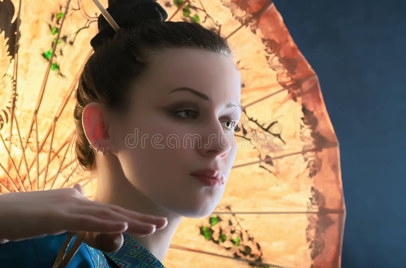 Portrait of a young woman with a Chinese umbrella. Stylized portrait of a young woman with the Chinese yellow paper umbrella on a blue background royalty free stock photo