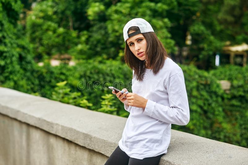Portrait of a young woman on a city street using a smartphone royalty free stock image