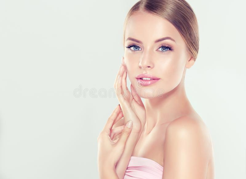 Portrait of young woman with clean fresh skin and soft, delicate make up. Woman is touching tenderly to own face. royalty free stock photos